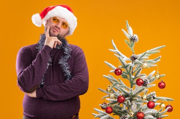 Nadenkende man van middelbare leeftijd met kerstmuts en klatergoud slinger rond de nek met glazen staande in de buurt van versierde kerstboom Gratis Foto