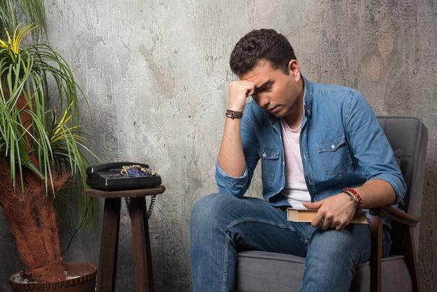 Nadenkende man zittend op een stoel met boek over marmeren achtergrond. hoge kwaliteit foto Gratis Foto