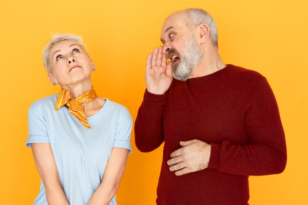 Nadenkende mooie zorgeloze vrouw van middelbare leeftijd opzoeken in wolken dromen, geen geschreeuw horen van haar ontevreden bejaarde echtgenoot met baard die hand naar zijn mond houdt en schreeuwt Gratis Foto