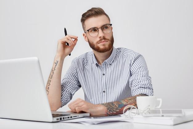Nadenkende slimme mannelijke student met trendy haido kijkt bedachtzaam opzij terwijl hij gedachten probeert te verzamelen, op cursuspapier werkt, voor geopende laptop zit, Gratis Foto