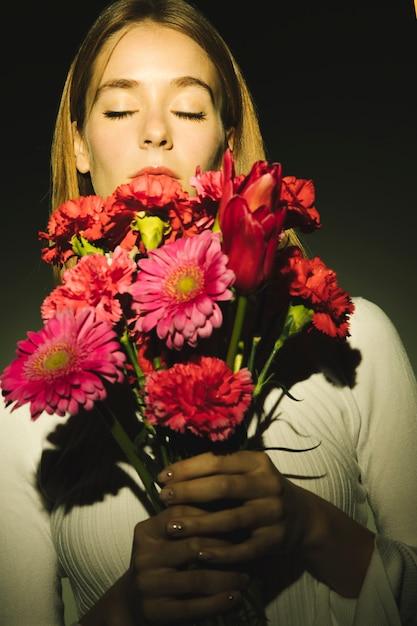 Nadenkende vrouw die roze bloemenboeket houdt Gratis Foto