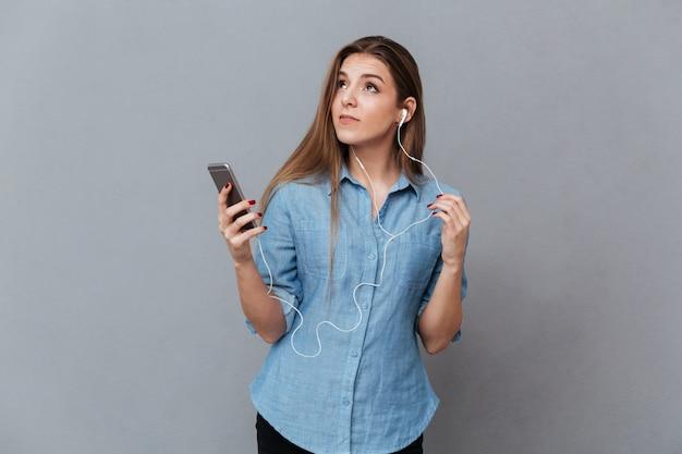 Nadenkende vrouw in overhemd het luisteren muziek op telefoon Gratis Foto