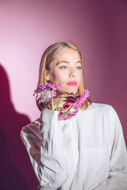Nadenkende vrouw met gerberabloemen in overhemdskoker Gratis Foto