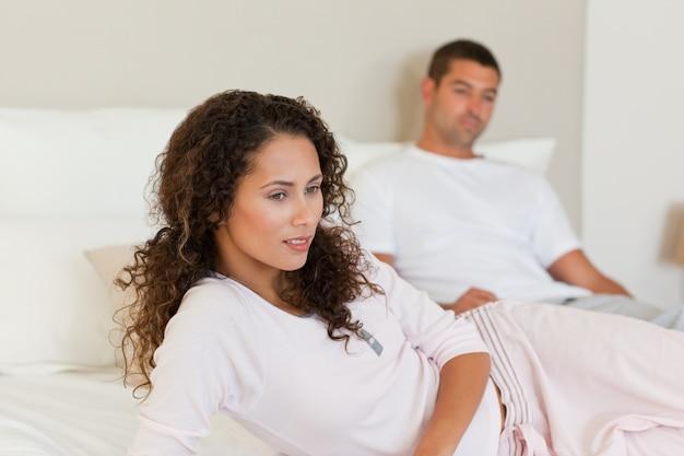 Nadenkende vrouw met haar echtgenoot op het bed Premium Foto