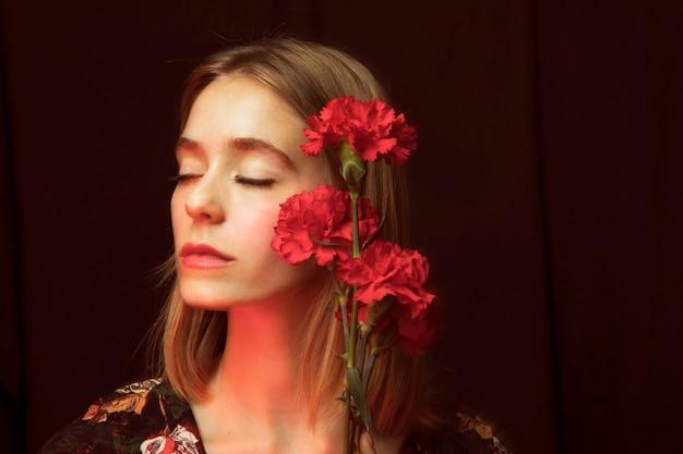 Nadenkende vrouw met rode anjers Gratis Foto