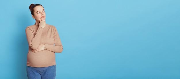 Nadenkende zwangere vrouw kijkt bedachtzaam opzij, houdt de hand op de kin, maakt plannen over de geboorte van een kind, droomt om moeder te worden, draagt een beige trui en spijkerbroek, geïsoleerd op een blauwe muur. Gratis Foto