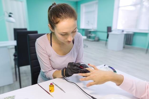 Nagel- en handverzorging in schoonheidssalon. jonge vrouw die professionele manicure doet Premium Foto
