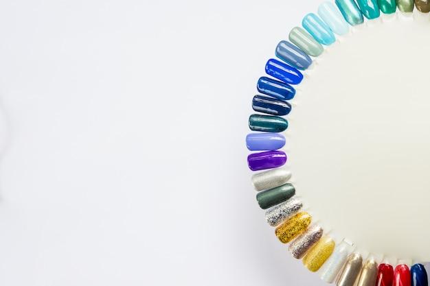 Nagellak in verschillende modekleuren. kleurrijke kattenoog 3d nagellak in tips geïsoleerd op een witte muur. glanzende gellak. vrouwelijke nail art. nail art design. veel blauwe en groene tinten Premium Foto
