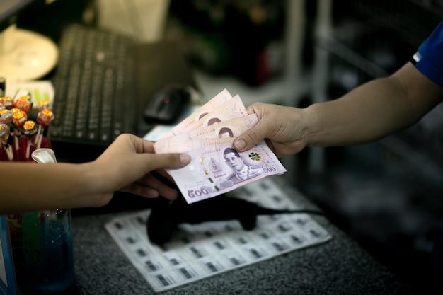 Nakhonsawan, thailand. de vrouw betaalt contant met de bankbiljetten van thailand. thais bahtgeld. Premium Foto