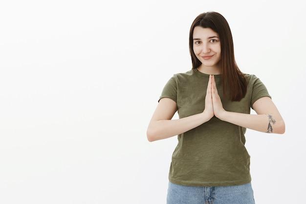 Namaste laat vrede met je zijn. portret van schattige en ontspannen knappe jonge 20s vrouw met tatoeage en bruin haar handpalmen tegen elkaar houden in gebed of boeddha pose glimlachend over grijze muur Gratis Foto