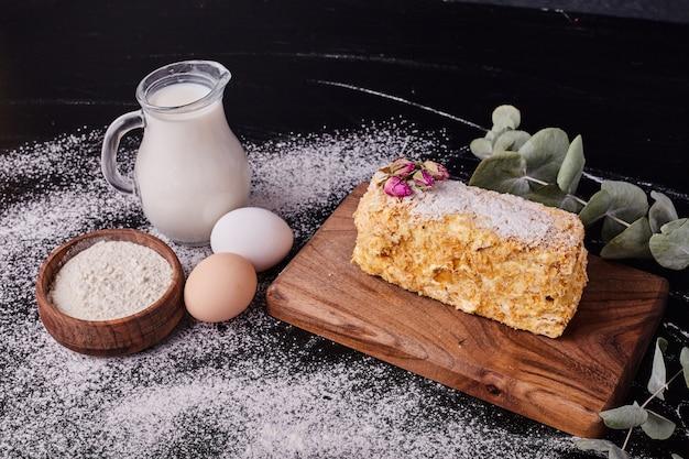 Napoleon cake versierd met gedroogde bloemzaden op zwarte tafel met ei, melk en kom meel. Gratis Foto