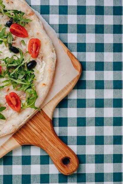 Napolitaanse pizza met tonijn, kaas, rucola, basilicum, tomaten, olijven, bestrooid met kaas op een houten tafel op een tafelkleed in een cel met een plek voor de tekst. Gratis Foto