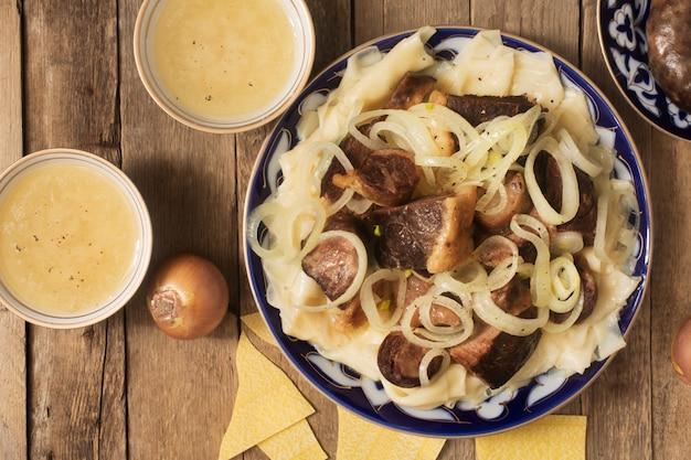 Nationale kazachse schotel - beshbarmak en bouillon in de kommen Premium Foto