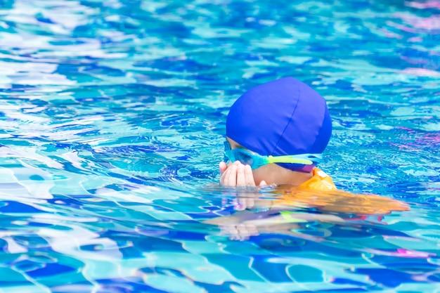 Natte pak aziatische jongen met duikbril is zwemmen in een zwembad Premium Foto