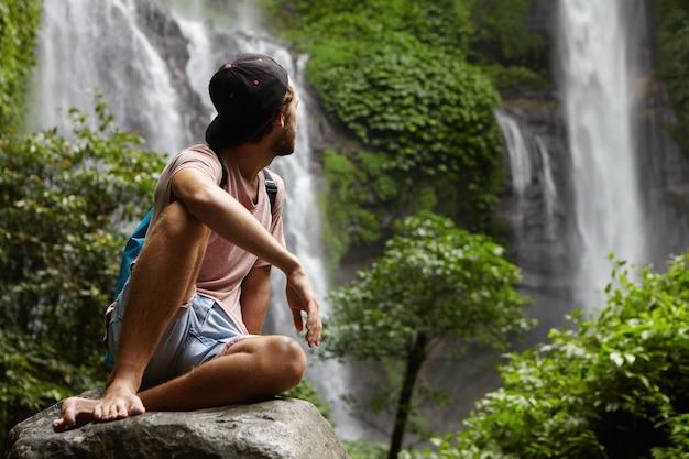 Natuur, dieren in het wild en reizen concept. jonge blootvoetse wandelaar die snapback zittend op grote steen draagt en geniet van een prachtig uitzicht om hem heen. hipster ontspannen diep in het regenwoud Gratis Foto