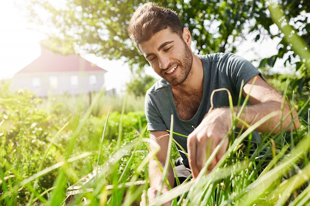 Natuur en milieu. jonge donkere bebaarde tuinman tijd doorbrengen in de tuin in de buurt van landhuis. man bladeren snijden en genieten van warm zomerweer in de schaduw van bomen Gratis Foto