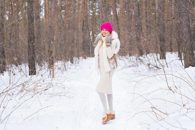 Natuur, mode en mensen concept - jonge aantrekkelijke blonde vrouw poseren in het winterpark. Premium Foto