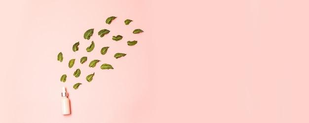 Natuurlijke anti-aging serum druppelaar in een glazen buis met muntblaadjes op roze Premium Foto