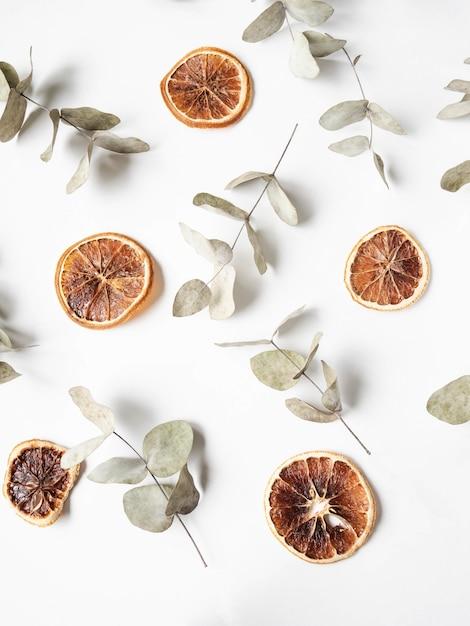 Natuurlijke creatieve samenstelling van droge takken van eucalyptus en droge sinaasappelplakken Premium Foto