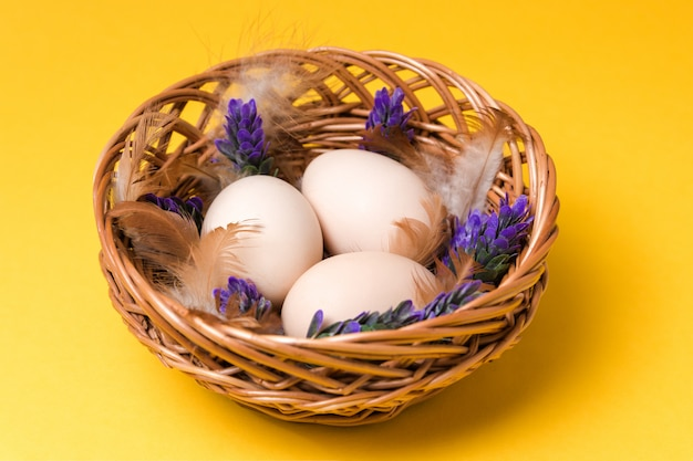 Natuurlijke ecologische eieren, veren en lavendel in een rieten mand op gele achtergrond met kopie ruimte. gelukkig pasen Premium Foto