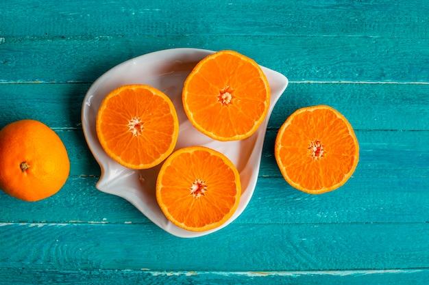 Natuurlijke en verse half gesneden sinaasappelen op plaat Gratis Foto