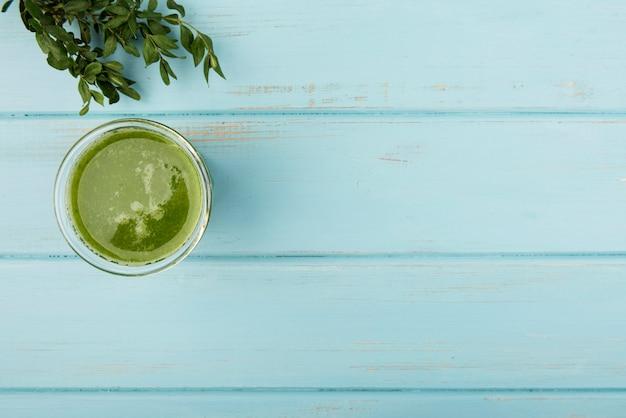 Natuurlijke groene smoothie in glas op houten achtergrond Gratis Foto