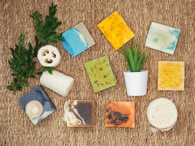 Natuurlijke handgemaakte huidverzorging. biologische stukken zeep met plantenextracten. stapelt zelfgemaakte stukken zeep met kruidenmateriaal. natuurlijke zeep met spa-accessoires. Premium Foto