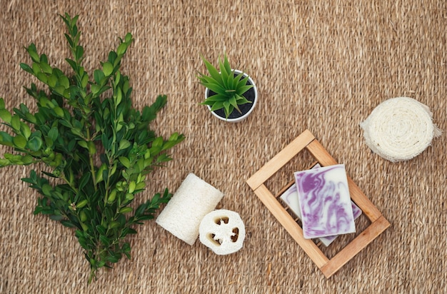 Natuurlijke handgemaakte zeep en accessoires voor lichaamsverzorging. diverse spa-gerelateerde objecten op stro achtergrond Premium Foto