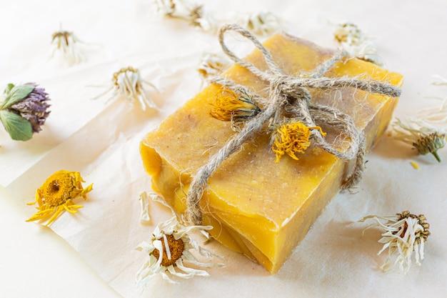 Natuurlijke handgemaakte zeep met kamille-extract. rond zijn gedroogde bloemen. Premium Foto