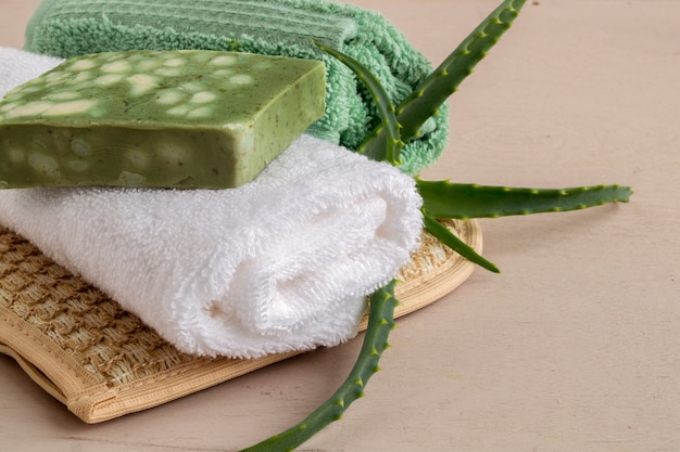 Natuurlijke handgemaakte zeep, washandje en handdoek op houten. Premium Foto