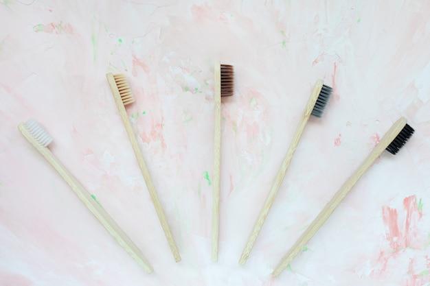 Natuurlijke houten tandenborstels van bamboe. plasticvrij en afvalvrij concept. bovenaanzicht, roze backgroundon Premium Foto