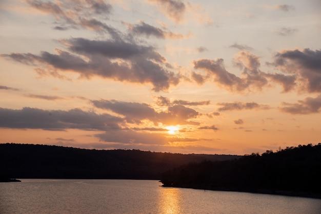 Natuurlijke zons ondergang sunrise over veld met berg Gratis Foto