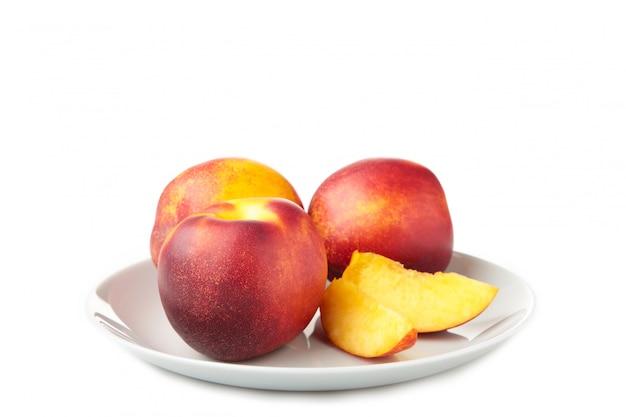 Nectarines in grijze plaat die op wit wordt geïsoleerd Premium Foto