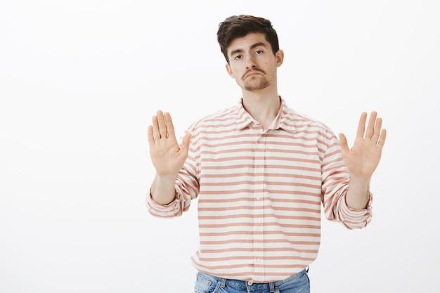 Nee, dank u wel. portret van onverschillige onbezorgde aantrekkelijke man met somber gezicht, palmen in stop of genoeg gebaar trekken, verkoper stoppen en aanbod afwijzen, staande Gratis Foto