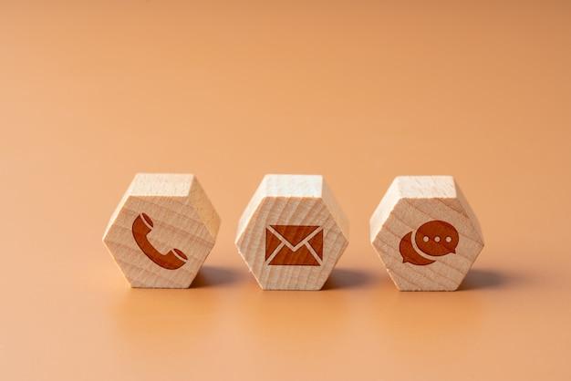 Neem contact op met ons pictogram op houten puzzel met hand Premium Foto