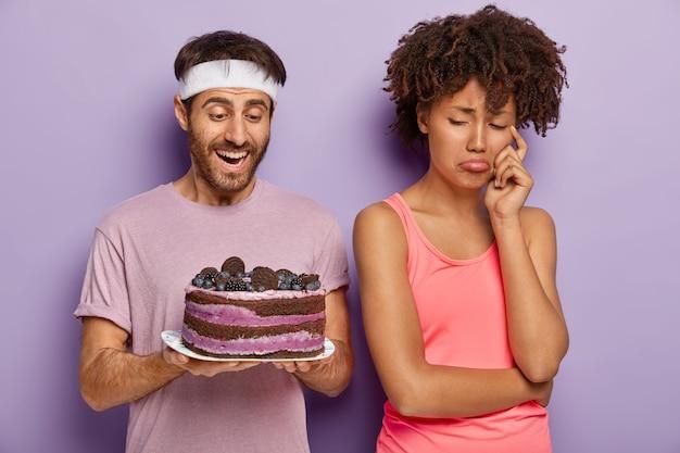 Neerslachtige, boze vrouw verandert van echtgenoot die smakelijke cake op bord houdt, heeft een droevige uitdrukking omdat ze geen zoete desserts kan eten om fit te blijven en slank leidt een gezonde levensstijl, weigert junkfood te eten Gratis Foto