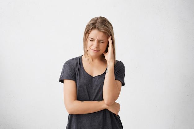 Negatieve menselijke emoties en gevoelens. ongelukkige jonge vrouw die lijdt aan erge hoofdpijn of migraine Gratis Foto