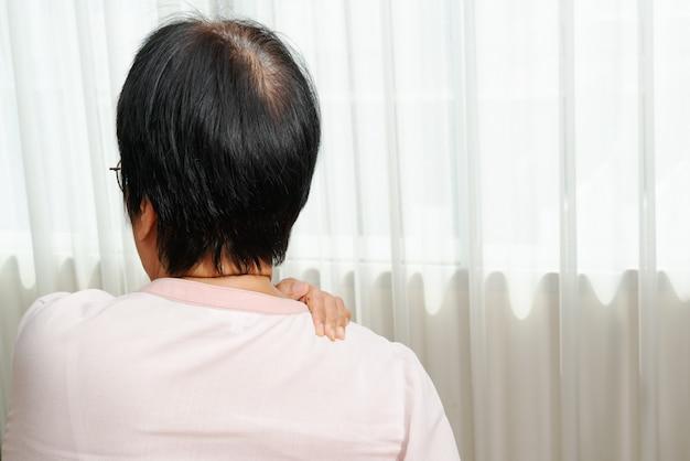 Nek- en schouderpijn, oude vrouw die lijdt aan nek- en schouderletsel, gezondheidsprobleemconcept Premium Foto