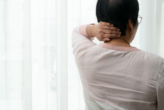 Nek- en schouderpijn, oude vrouw die lijdt aan nek- en schouderletsel Premium Foto