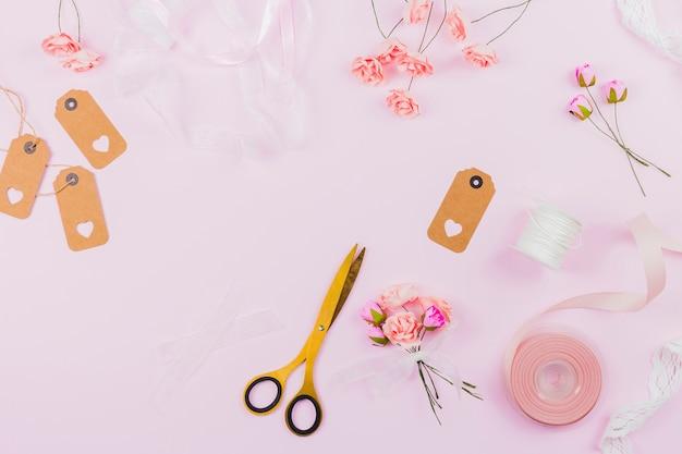 Nep kunstbloemen met lint; label en schaar op roze achtergrond Gratis Foto