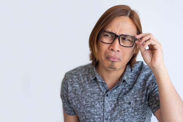 Nerdy aziatische kerel die voor camera voor de gek houdt Gratis Foto