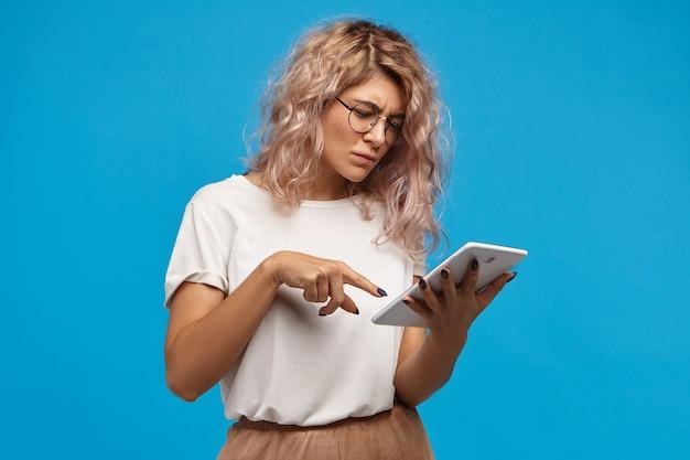 Nerdy ernstige hipster meisje in ronde bril surfen op internet op touchpad digitale tablet, foto's scrollen via sociale netwerken Gratis Foto