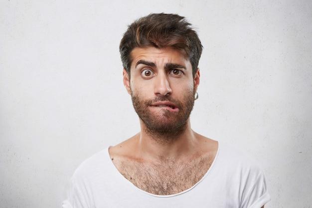 Nerveus twijfelachtig mannetje met stijlvol kapsel en baard die zijn wenkbrauw fronst, bijtende lippen die een verbaasde blik hebben en een serieuze beslissing gaan nemen. verrast macho man uiting geven aan zijn gevoelens en emoties Gratis Foto