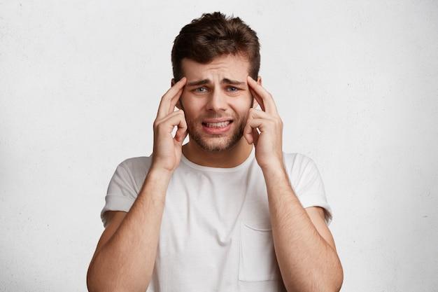 Nerveuze aantrekkelijke man in wanhoop heeft een ontevreden uitdrukking, houdt de vingers op de slapen, kleedt zich nonchalant, klemt zijn tanden op elkaar, Gratis Foto