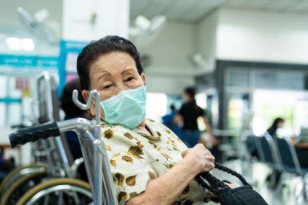 Nerveuze aziatische oudere vrouw van 80 jaar die wacht om een dokter te ontmoeten in het overheidsziekenhuis. Premium Foto