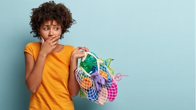 Nerveuze zwarte vrouw met krullend haar, bedekt de mond, kijkt bezorgd naar de zak met plastic afval, toont negatieve emoties, neemt deel aan een ecologische campagne tegen milieuvervuiling. socail werk Gratis Foto