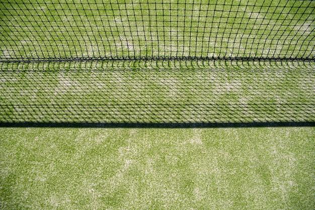 Net van een tennisbaan die zijn schaduw op het gras projecteert Premium Foto