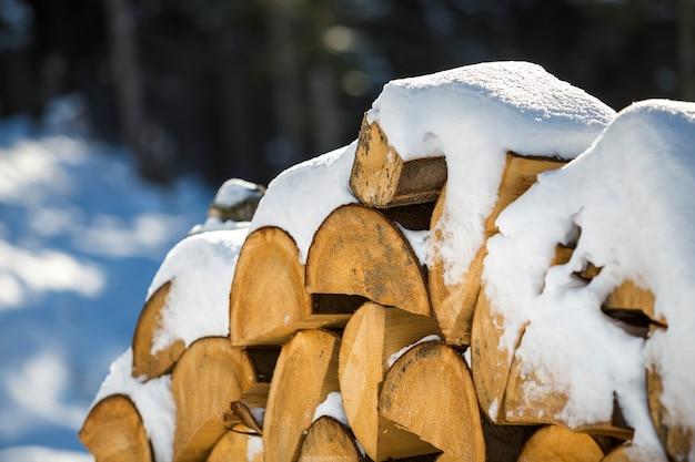 Netjes opgestapelde stapel gehakte droge stammen hout bedekt met sneeuw buiten op heldere koude zonnige winterdag, abstracte achtergrond, brandhout logboeken voorbereid voor de winter, klaar om te branden. Premium Foto