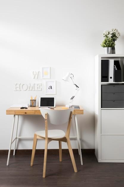 Nette en opgeruimde werkruimte met tablet op bureau Gratis Foto