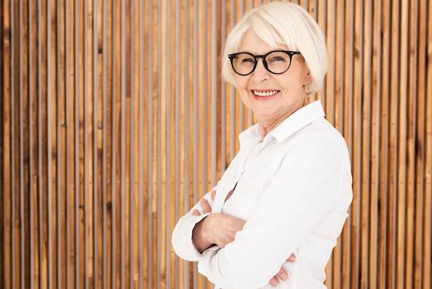 Nette oude vrouw met brillen die zich naast een houten muur bevinden Gratis Foto